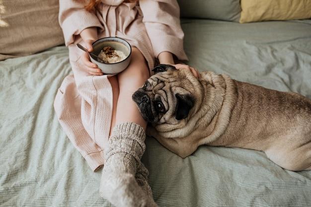 Dziewczyna w wełnianych skarpetkach je śniadaniową owsiankę w łóżku ze swoim przyjacielem mopsem.