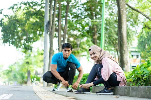 Dziewczyna w welonie i mężczyzna kucają, przygotowując się do naprawienia sznurowadeł przed bieganiem w parku