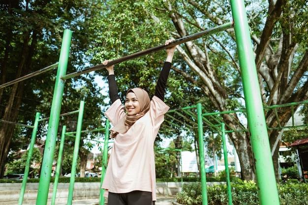Dziewczyna w welonie podciąga się, aby poprawić wydolność płuc i schudnąć, ćwicząc na świeżym powietrzu w parku