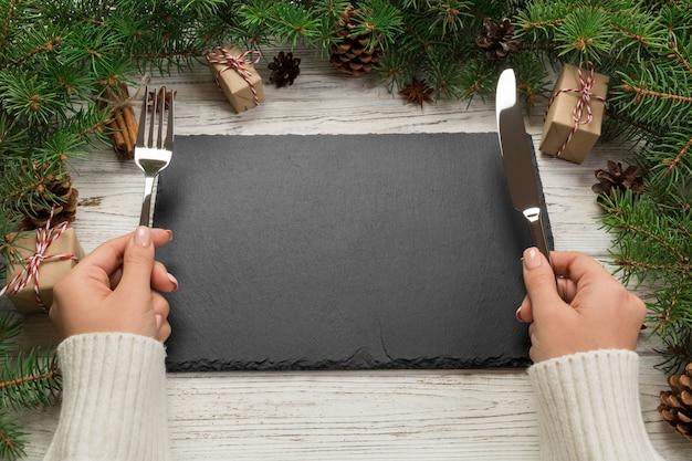 Dziewczyna w widoku perspektywicznym trzyma w ręku widelec i nóż i jest gotowa do jedzenia, pusty czarny prostokątny talerz z łupków na drewniane święta, koncepcja świątecznej kolacji z wystrojem nowego roku