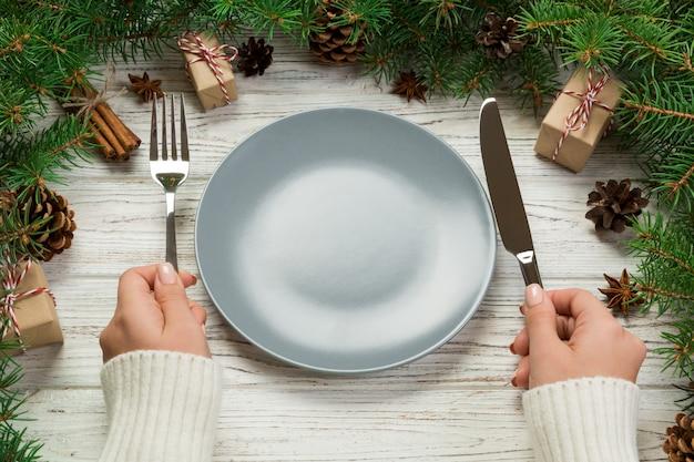Dziewczyna w widoku perspektywicznym trzyma w ręku widelec i nóż i jest gotowa do jedzenia.