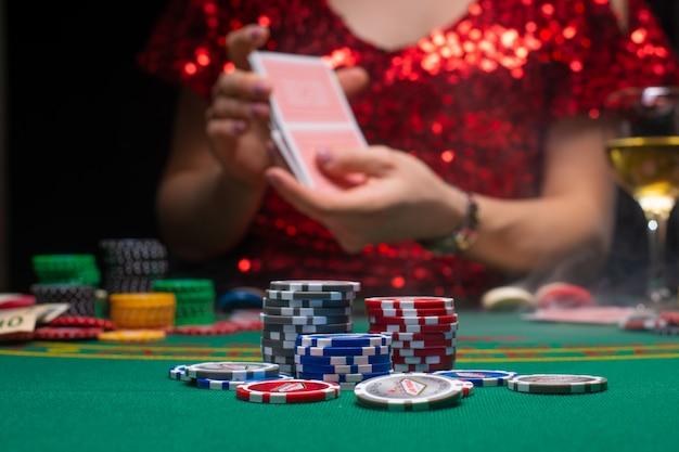 Dziewczyna w wieczorowej czerwonej sukience bawi się w kasynie