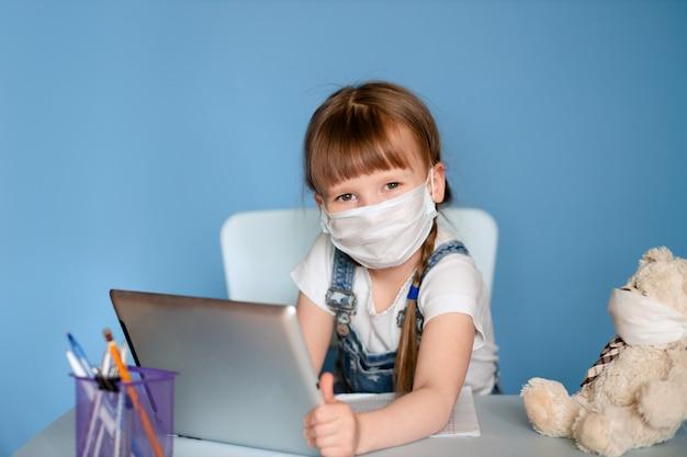 Dziewczyna w wieku 5-6 lat siedząca przy stole wykonuje zadania domowe na tablecie. izoluj na niebieskiej ścianie. koronawirus, zamaskowane dziecko.