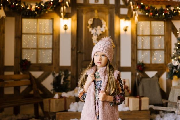 Dziewczyna w wieku pięciu lub sześciu lat w różowej dzianej czapce z pomponem w różowej futrzanej kamizelce stoi naprzeciwko świątecznego domu