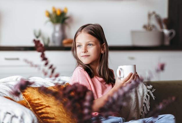 Dziewczyna w wieku przedszkolnym siedzi na kanapie z białą filiżanką w dłoniach i wygląda przez okno. śliczny zamyślony dzieciak spędzający czas w domu