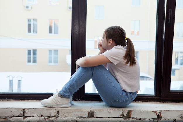 Dziewczyna w wieku przedszkolnym smutna w pobliżu okna, obejmująca kolana