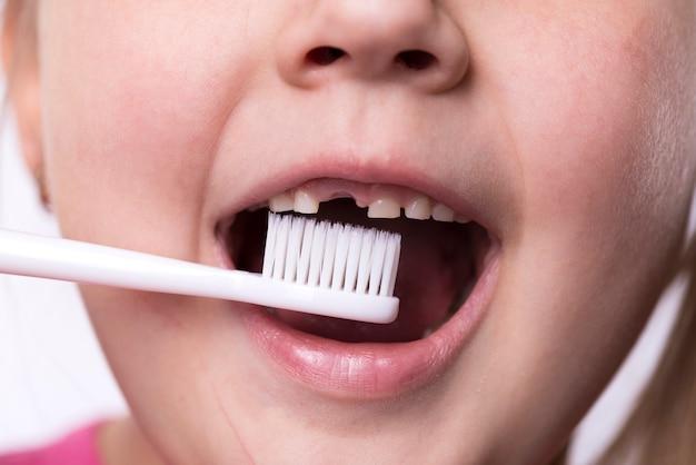 Dziewczyna w wieku przedszkolnym szczotkuje zęby