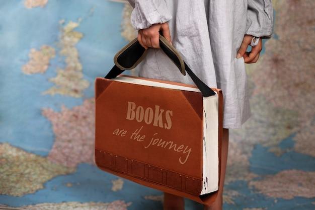Dziewczyna w wieku przedszkolnym trzymająca wielką książkę jak walizkę do podróży - otwiera świat z książką