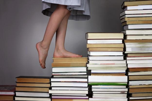 Dziewczyna w wieku przedszkolnym wchodząca po schodach książek z jednego poziomu edukacji na drugi