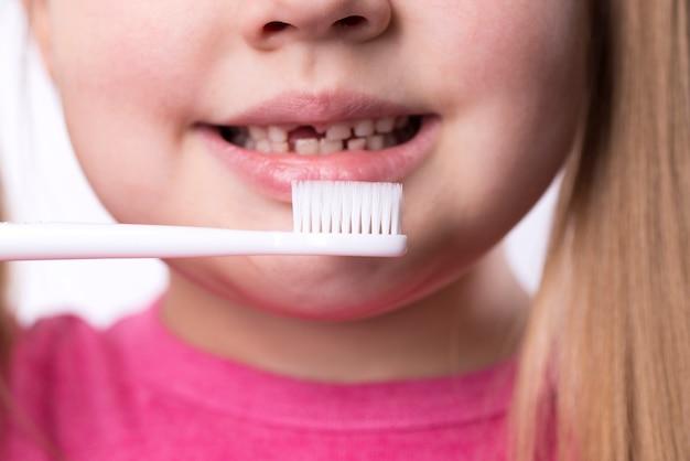 Dziewczyna w wieku przedszkolnym z pierwszymi dorosłymi siekaczami i szczoteczką do zębów
