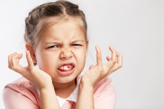Dziewczyna w wieku szkolnym w różowym swetrze jest zła. biała ściana. zbliżenie.