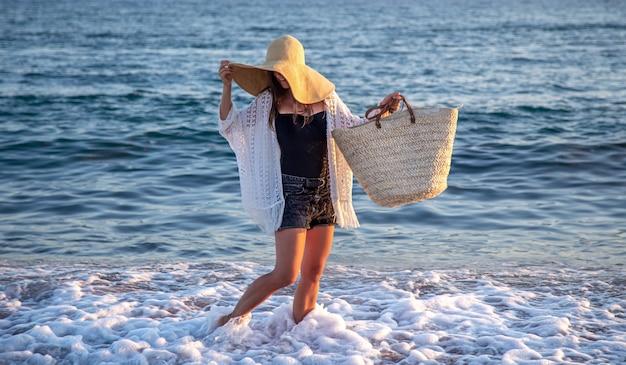 Dziewczyna w wielkim kapeluszu i wiklinowej torbie spaceruje wzdłuż wybrzeża. koncepcja wakacji letnich.