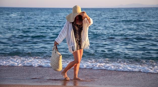 Dziewczyna w wielkim kapeluszu z wiklinową torbą spaceruje brzegiem morza. koncepcja wakacji letnich.