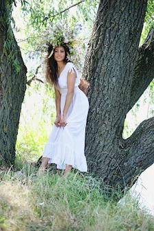 Dziewczyna w wieńcu z polnych kwiatów pod drzewem