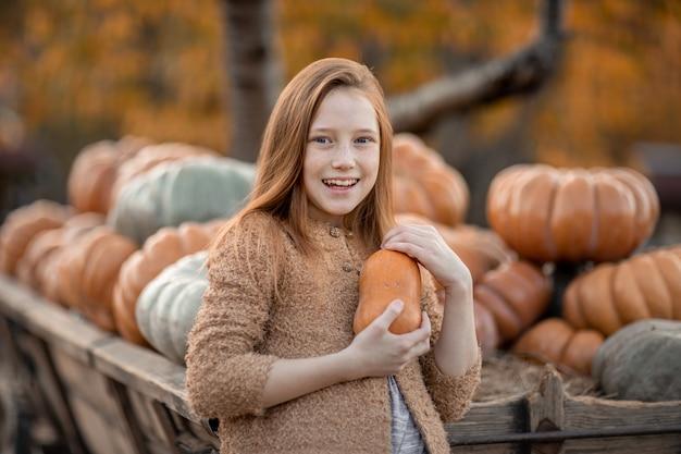 Dziewczyna w wiosce na farmie trzyma w rękach dojrzałą dynię.
