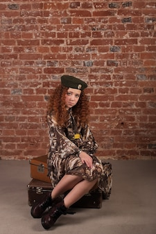 Dziewczyna w wojskowym stroju siedzi na walizce