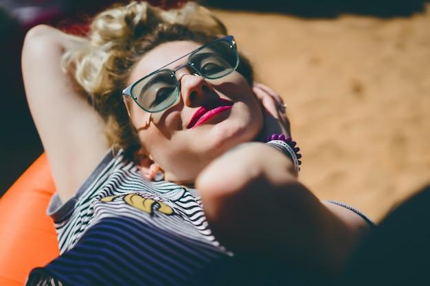 Dziewczyna w zabytkowe okulary z tatuażami zbliżenie portret na ulicy podczas pikniku z przyjaciółmi. chłodna dziewczyna