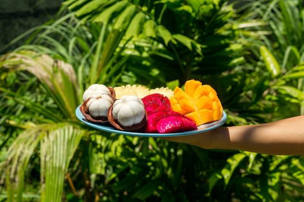 Dziewczyna w zielonej dżungli trzyma talerz ze świeżo pokrojonymi i obranymi owocami tropikalnymi.