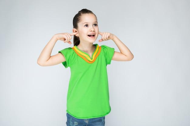 Dziewczyna w zielonej koszulce i niebieskich dżinsach na szaro.