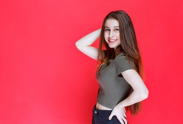Dziewczyna w zielonej koszuli dająca uśmiechnięte i uwodzicielskie pozy.