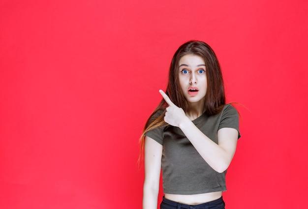 Dziewczyna w zielonej koszuli pokazująca coś na zachodzie.