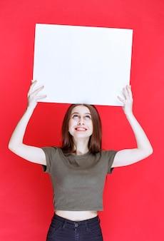 Dziewczyna w zielonej koszuli trzyma duże puste kwadratowe biurko.