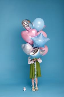 Dziewczyna w zielonej sukience zakrywa twarz garścią balonów na niebieskiej powierzchni