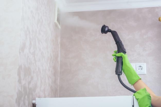 Dziewczyna w zielonych rękawiczkach czyści okap kuchenny w mieszkaniu za pomocą odkurzacza parowego