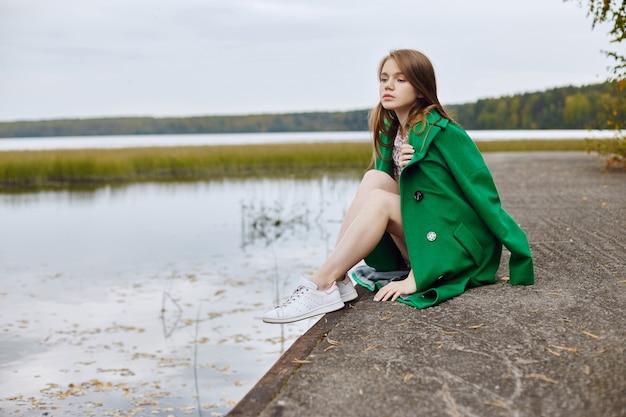 Dziewczyna w zielonym płaszczu idzie wzdłuż nabrzeża jeziora w pochmurny, jesienny dzień. jesienna moda i odzież, żółte opadłe liście unoszą się w wodzie. romantyczny nastrój