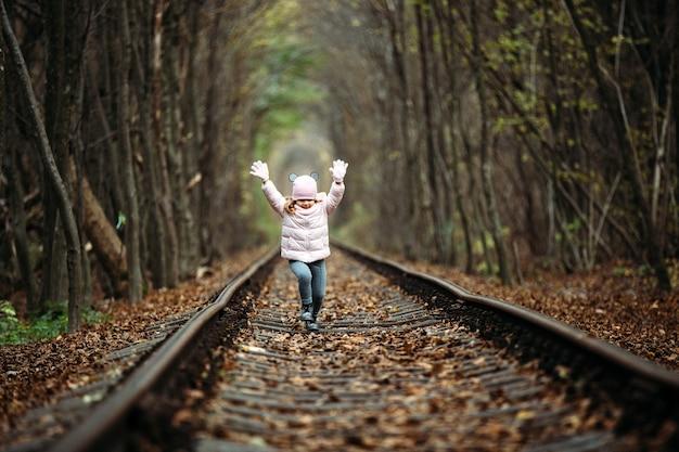 Dziewczyna w zielonym tunelu kolejowym. tunel miłości jesienią. kolej i tunel z drzew