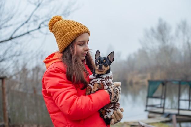 Dziewczyna w zimowe ubrania. nastolatka w pomarańczowej kurtce, kapeluszu i szaliku. dziewczyna i chihuahua.