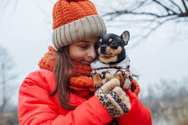 Dziewczyna w zimowe ubrania. nastolatka w pomarańczowej kurtce, pomarańczowym kapeluszu i szaliku. dziewczyna i chihuahua