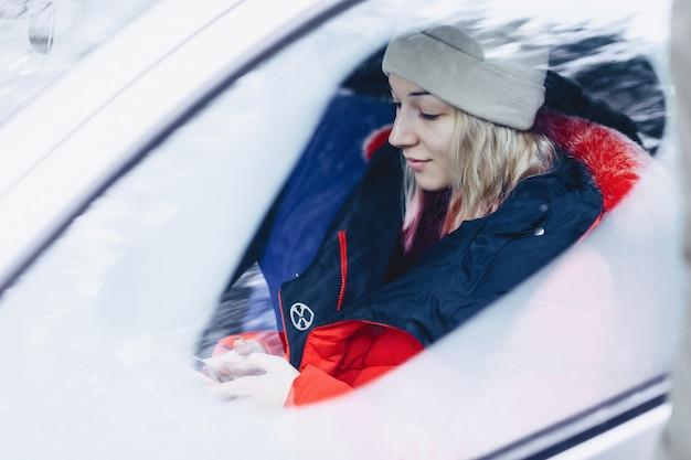 Dziewczyna w zimowe ubrania w samochodzie patrzy na telefon