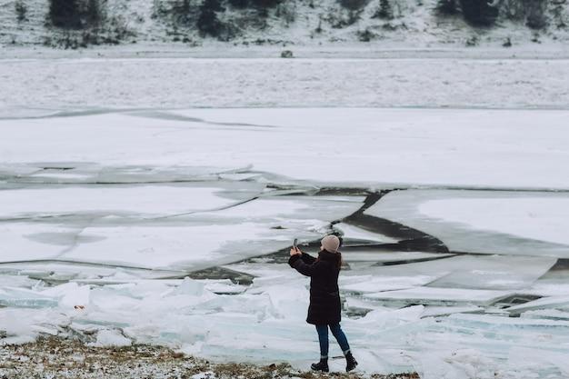 Dziewczyna w zimowych ubraniach robi sobie selfie na tle popękanego lodu na rzece.