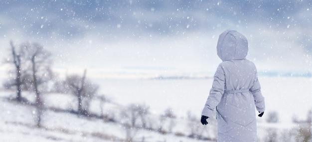 Dziewczyna w zimowym płaszczu na wzgórzu podczas zimowego spaceru w silnej śnieżycy