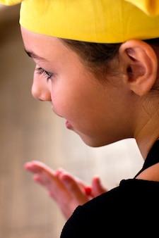 Dziewczyna w żółtej czapce szefa kuchni i czarnym fartuchu wesoło patrzy w lewo