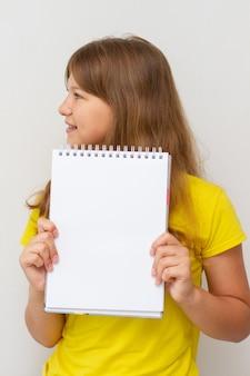 Dziewczyna w żółtej koszulce z pustym notatnikiem w rękach. dziewczynka dziecko trzyma pustą książkę. wolne miejsce na tekst.