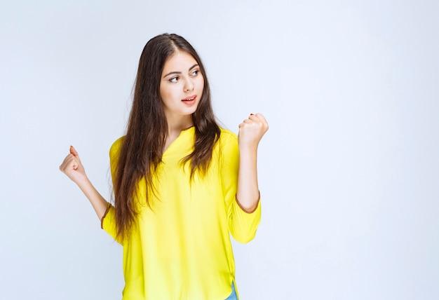 Dziewczyna w żółtej koszuli pokazując pięść na znak sukcesu.