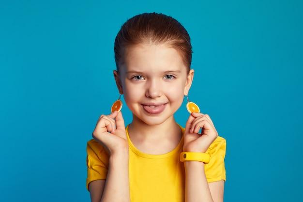 Dziewczyna w żółtej koszuli pokazująca język i pomarańczowe kolczyki na tle niebieskiej ściany