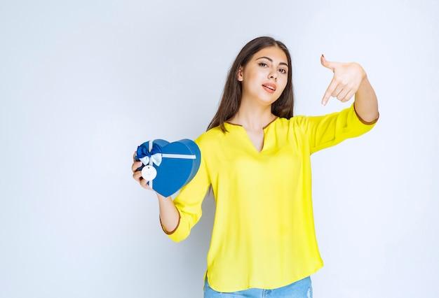 Dziewczyna w żółtej koszuli trzyma i promuje pudełko w kształcie niebieskiego serca.
