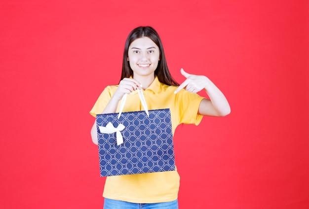 Dziewczyna w żółtej koszuli trzyma niebieską torbę na zakupy z wzorami i woła kogoś, żeby podszedł, żeby ją zabrać