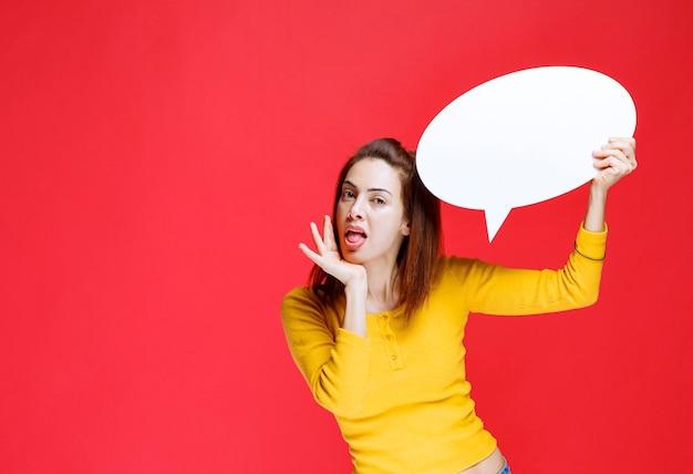 Dziewczyna w żółtej koszuli trzyma owalną tablicę informacyjną i wygląda na zdezorientowaną i zamyśloną.