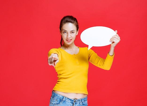 Dziewczyna w żółtej koszuli trzyma owalną tablicę informacyjną i zauważa osobę z przodu