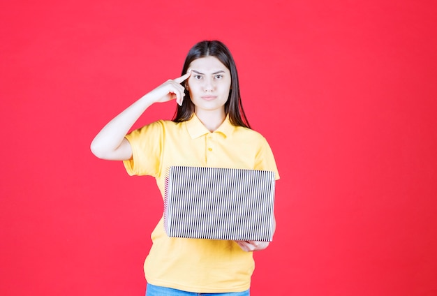 Dziewczyna w żółtej koszuli trzyma srebrne pudełko i wygląda na zdezorientowaną i zamyśloną
