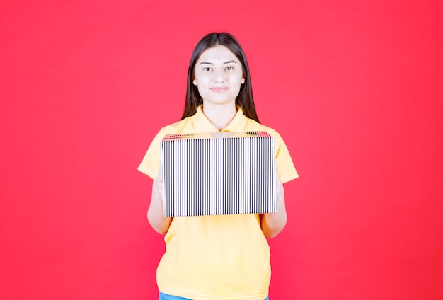 Dziewczyna w żółtej koszuli trzyma srebrne pudełko na prezent