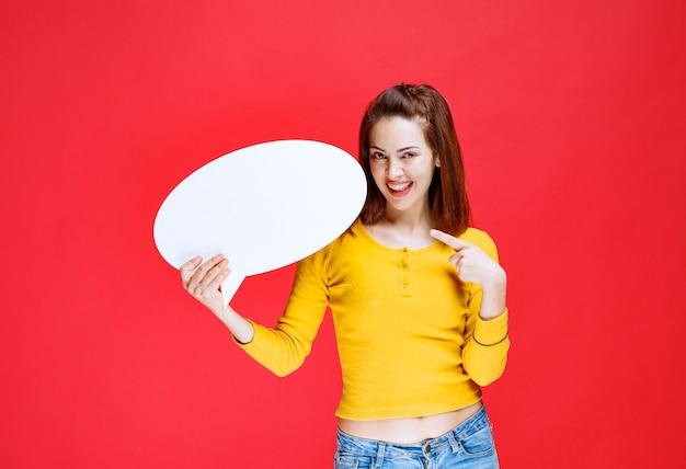 Dziewczyna w żółtej koszuli trzyma tablicę informacyjną owalny.