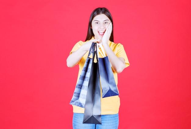 Dziewczyna w żółtej koszuli trzyma wiele niebieskich toreb na zakupy i wygląda na zaskoczoną