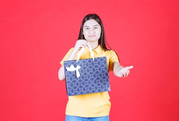 Dziewczyna w żółtej koszuli trzymająca niebieską torbę na zakupy i zapraszająca kogoś