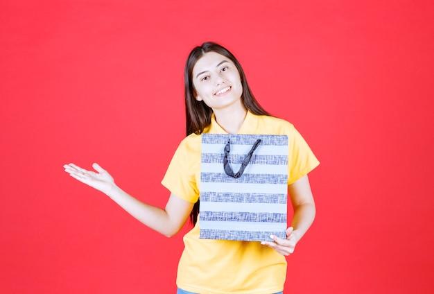 Dziewczyna w żółtej koszuli trzymająca niebieską torbę na zakupy z wzorami