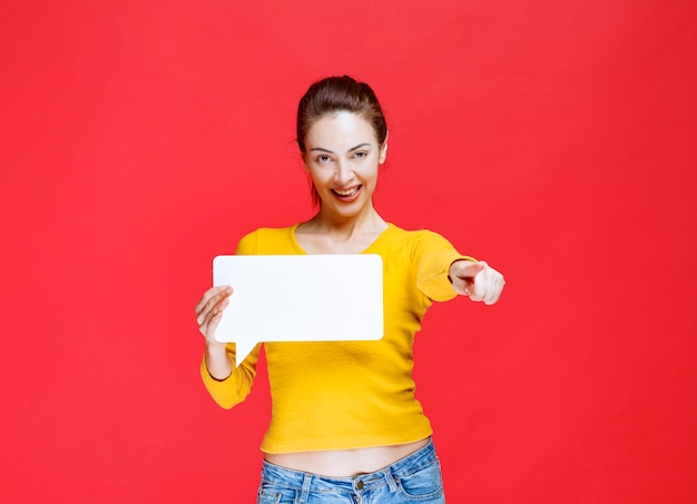 Dziewczyna w żółtej koszuli trzymająca prostokątną tablicę informacyjną i wskazującą osobę przed sobą